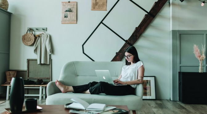 content-young-woman-using-laptop-in-modern-living-room-4050334